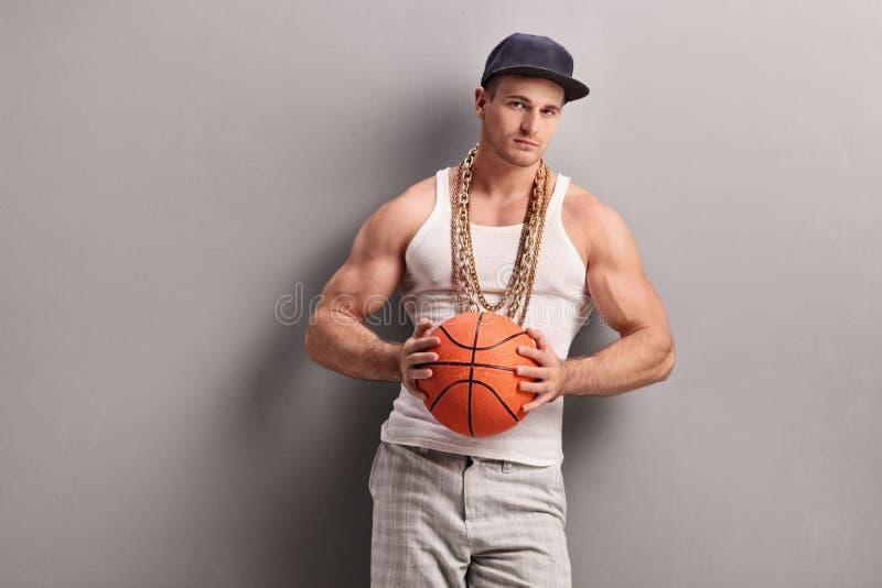 Homem com a corrente do ouro que guarda um basquetebol fotos de stock