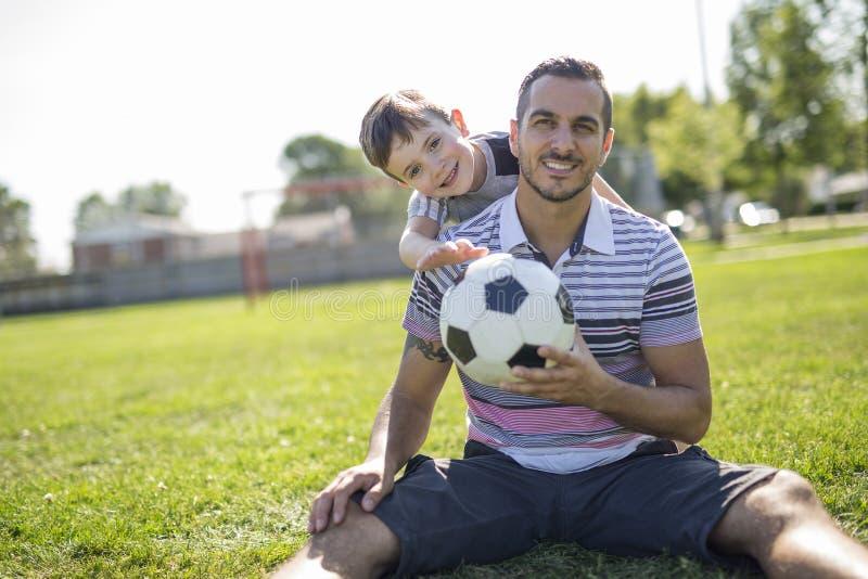 Homem com a criança que joga o futebol no campo imagem de stock