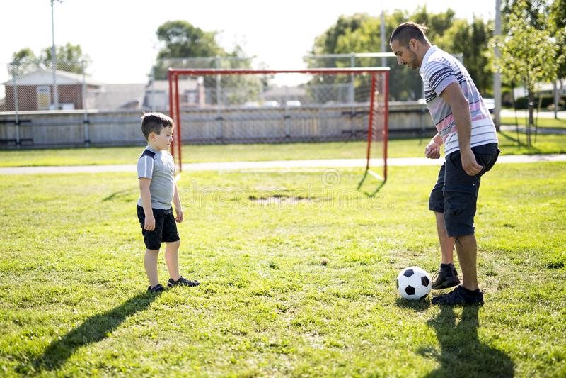 Homem com a criança que joga o futebol no campo imagens de stock