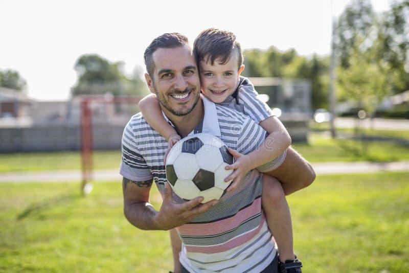 Homem com a criança que joga o futebol no campo fotografia de stock royalty free