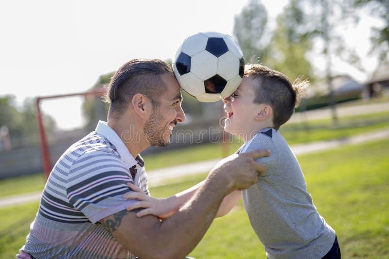 Homem com a criança que joga o futebol no campo foto de stock royalty free