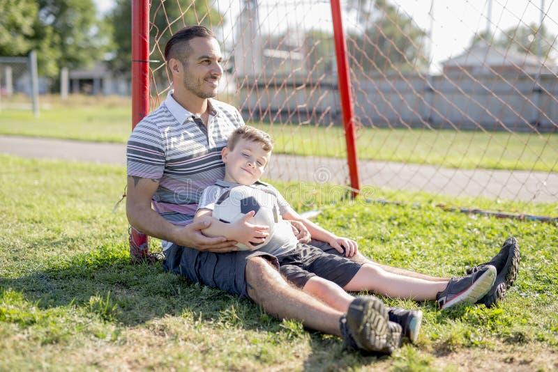 Homem com a criança que joga o futebol no campo fotos de stock royalty free