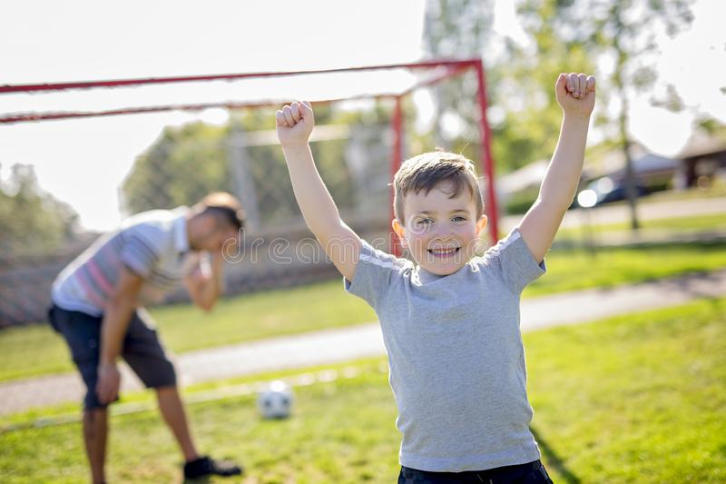 Homem com a criança que joga o futebol no campo fotos de stock