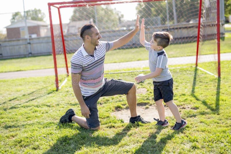 Homem com a criança que joga o futebol no campo imagem de stock royalty free