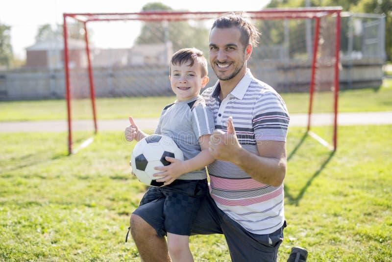 Homem com a criança que joga o futebol no campo imagens de stock royalty free