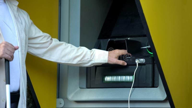 Homem com deficiência visual inserindo senha na máquina atm, retirando dinheiro fotografia de stock