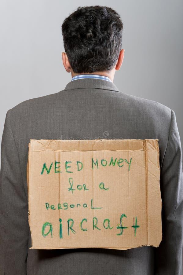 Homem com dinheiro da necessidade do sinal do cartão fotografia de stock