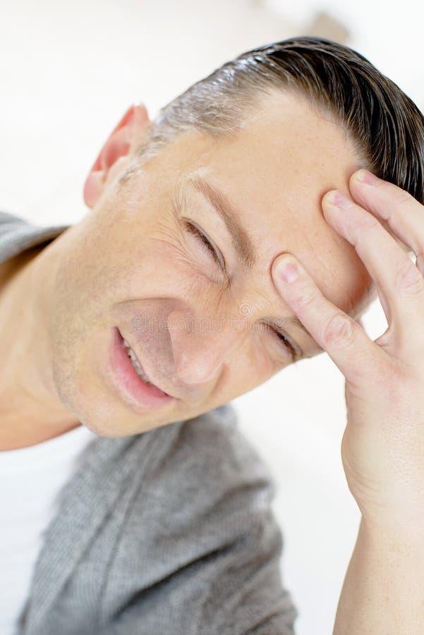Homem com dor de cabeça severa imagem de stock
