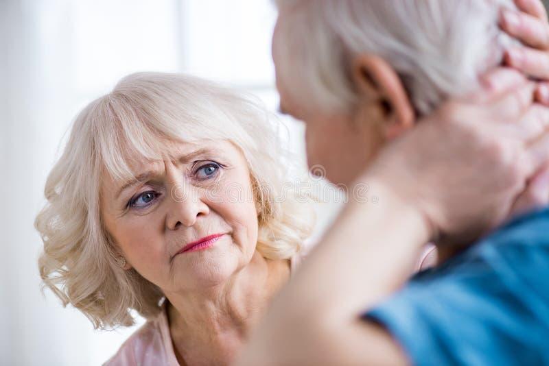 Homem com dor de pescoço e mulher interessada em casa fotografia de stock royalty free