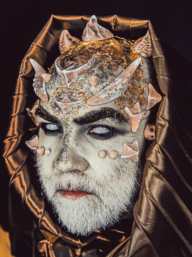 Homem com espinhos ou verrugas, cara coberta com os brilhos O homem superior com barba branca vestiu-se como o monstro Estrangeir imagens de stock