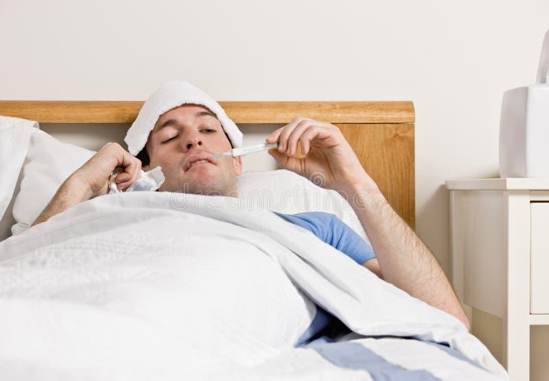Homem com a febre que coloca na cama que toma a temperatura imagem de stock royalty free