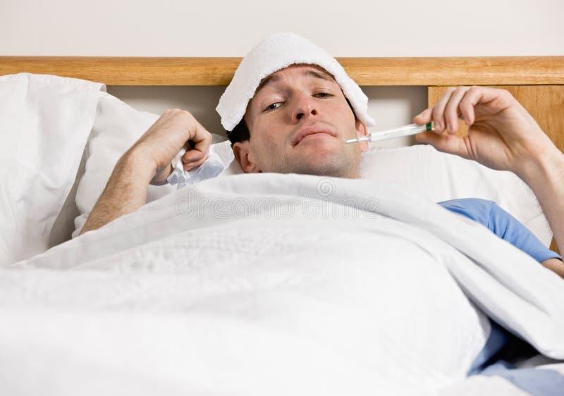Homem com a febre que coloca na cama que toma a temperatura fotos de stock royalty free