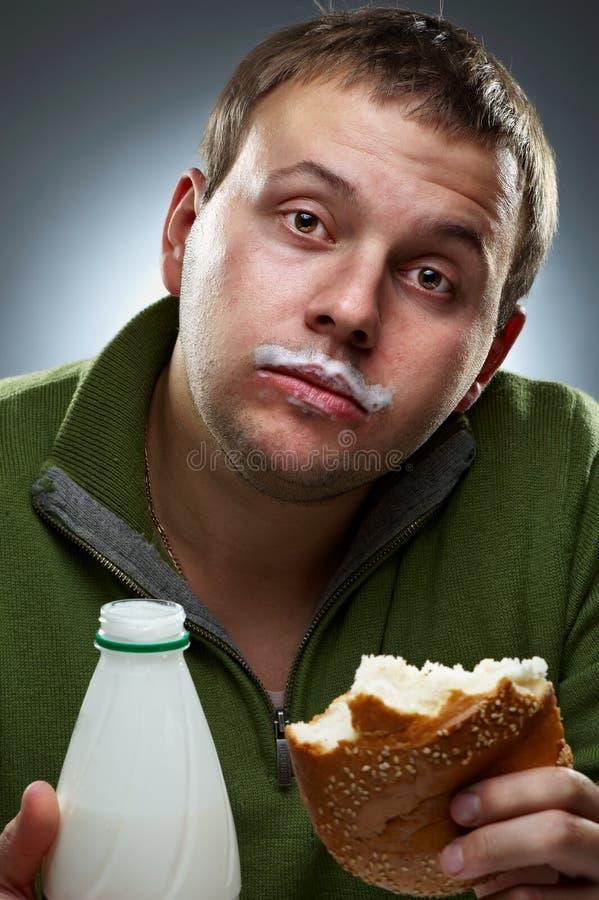Homem com fome com a boca cheia do pão fotos de stock royalty free