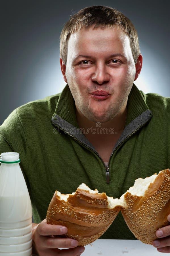Homem com fome com a boca cheia do pão fotografia de stock