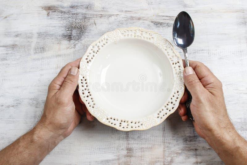 Homem com fome que espera sua refeição sobre a bacia vazia fotos de stock
