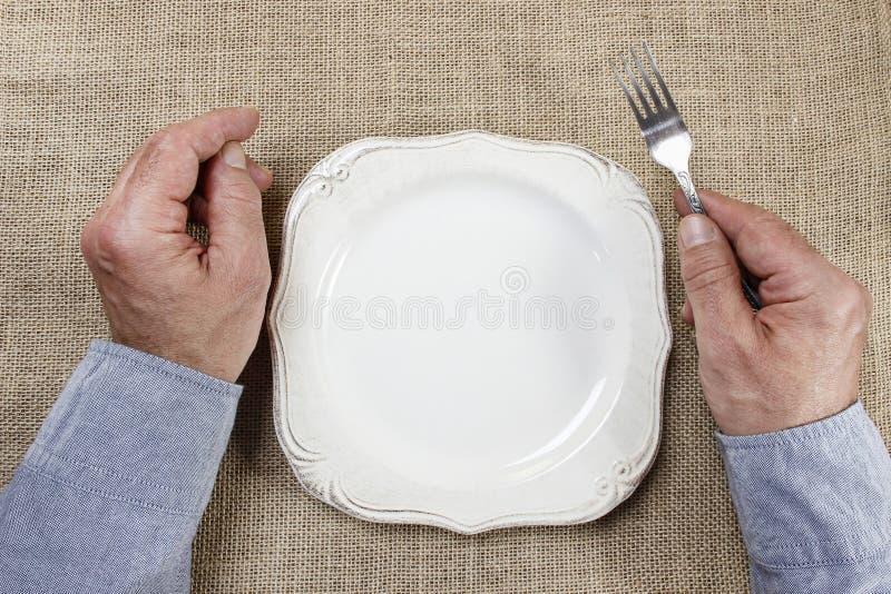 Homem com fome que espera sua refeição sobre a placa vazia fotografia de stock royalty free