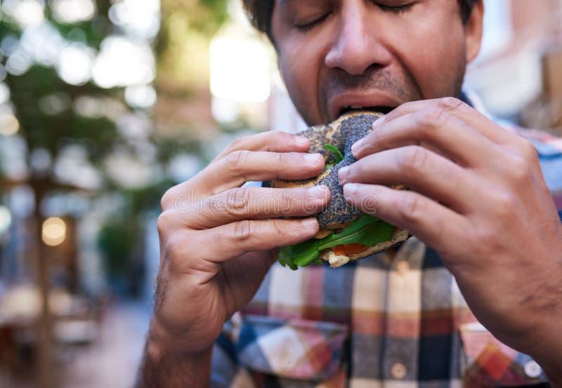 Homem com fome que senta-se fora de comer um bagel delicioso da semente de papoila fotos de stock