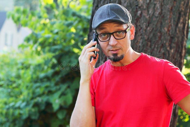 Homem com goatee que fala no telefone de pilha foto de stock
