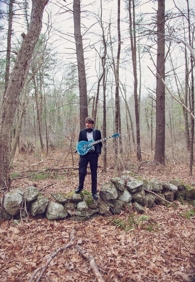 Homem com guitarra no bosque foto de stock royalty free