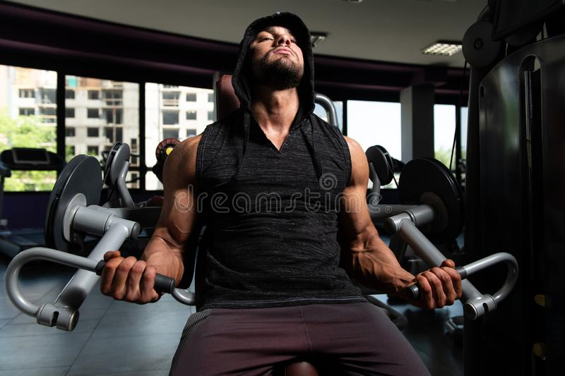 Homem com Hoodie que exercita o b?ceps no Gym foto de stock royalty free