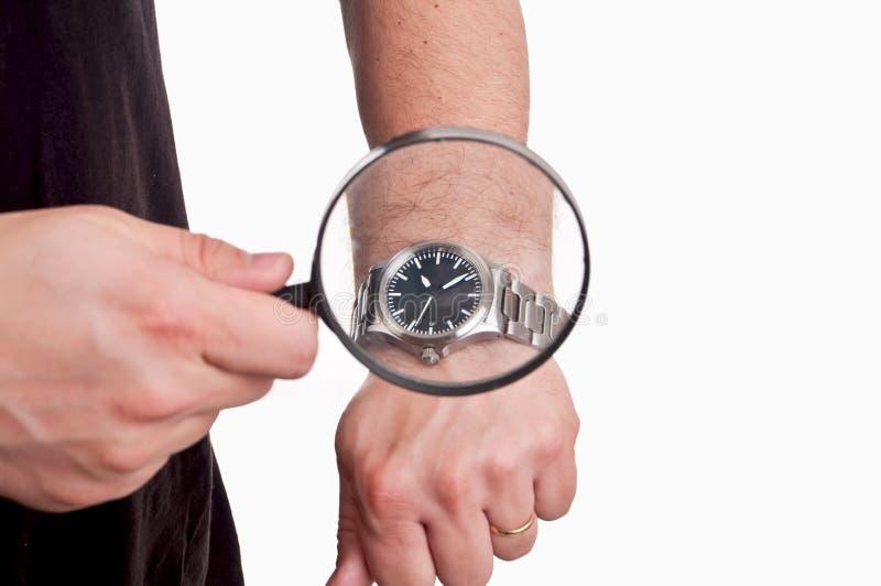 Homem com a lente de aumento à disposição que olha seu relógio no backgro branco foto de stock royalty free