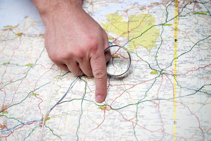 Homem com lente de aumento que aponta em um mapa fotografia de stock