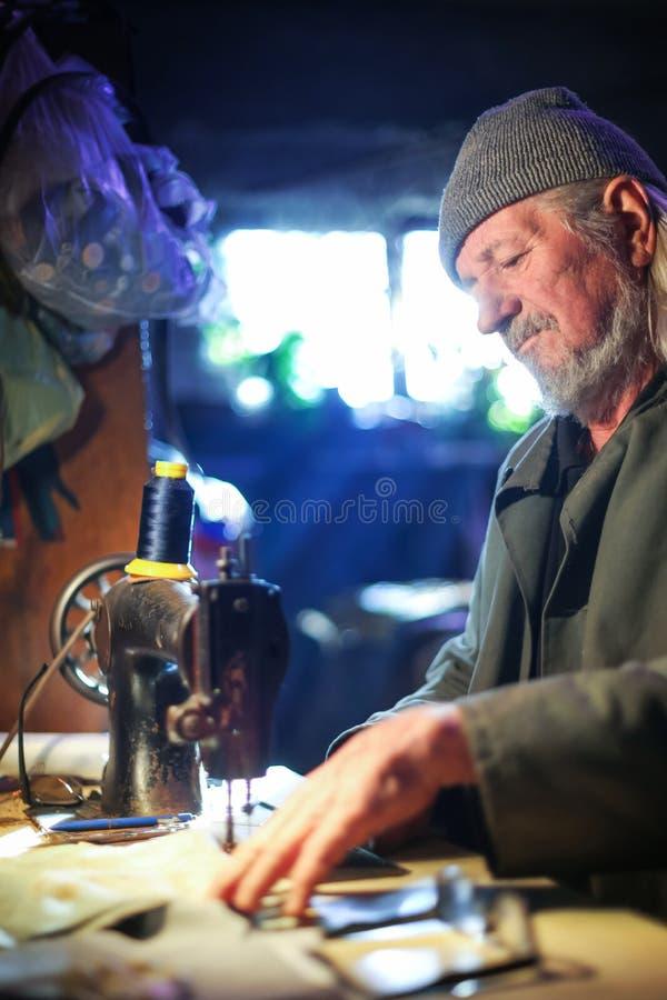Homem com máquina de costura imagens de stock royalty free