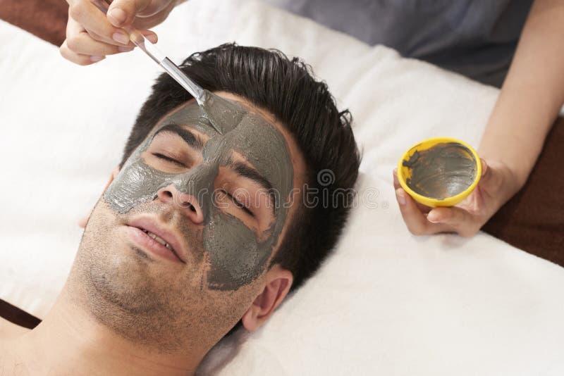 Homem com máscara do facial da argila fotos de stock royalty free