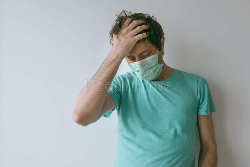 Homem com máscara que tem enxaqueca como sintomas de Covid- 19 foto de stock
