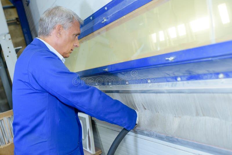 Homem com mãos em limpar com jato de areia a máquina fotos de stock royalty free