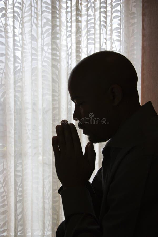 Homem com mãos na oração imagens de stock