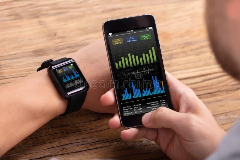 Homem com m?bil e taxa da pulsa??o do cora??o da exibi??o de Smartwatch imagens de stock