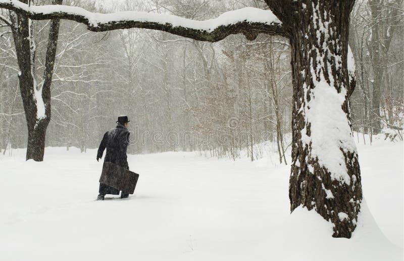 Homem com mala de viagem que anda na neve imagens de stock royalty free