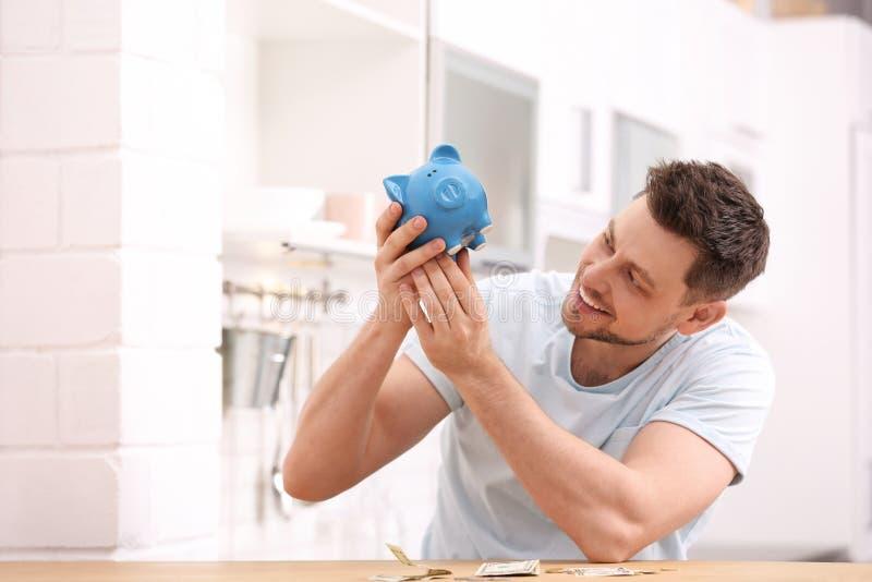 Homem com mealheiro e dinheiro em casa fotografia de stock royalty free