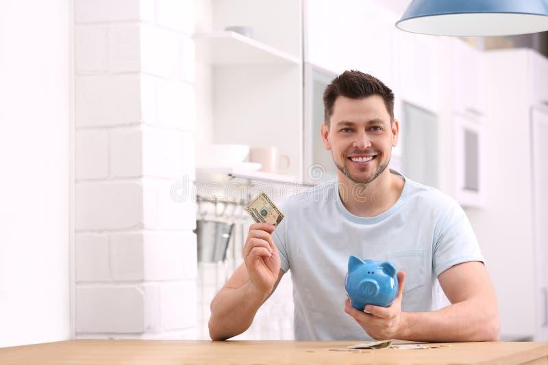 Homem com mealheiro e dinheiro em casa fotografia de stock