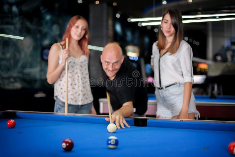 Homem com a menina dois bonita que joga a sinuca foto de stock royalty free
