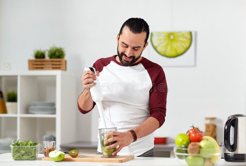 Homem com misturador que cozinha a cozinha do alimento em casa fotografia de stock royalty free