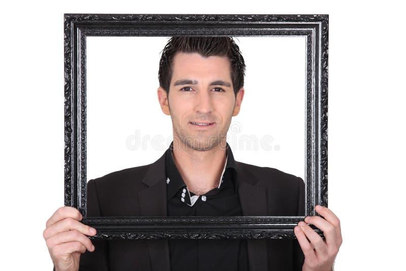Homem com moldura para retrato fotografia de stock