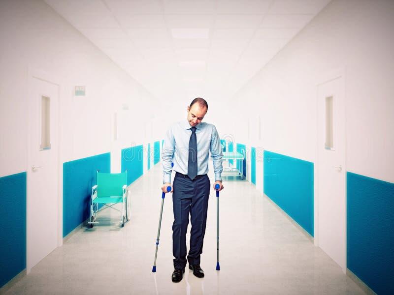 Homem com a muleta no hospital imagens de stock