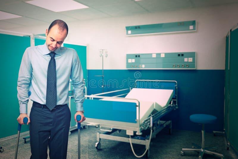 Homem com a muleta no hospital imagem de stock