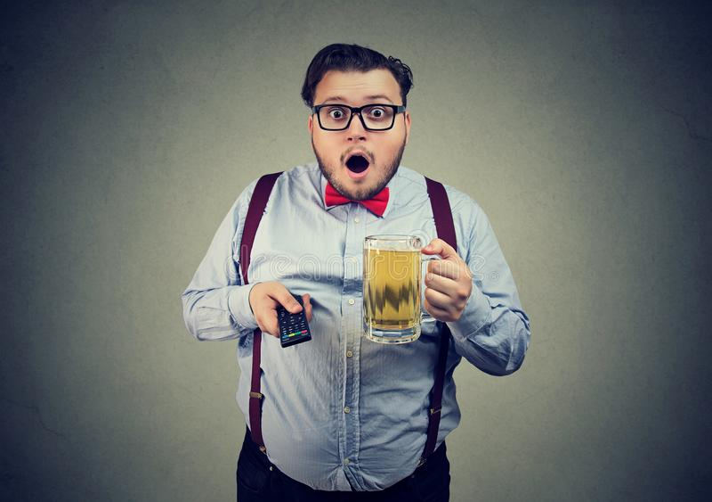 Homem com notícia chocante de observação da cerveja imagens de stock