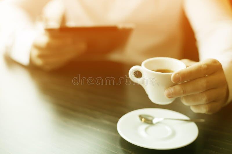 Homem com notícia da leitura do café e do tablet pc em motning fotografia de stock