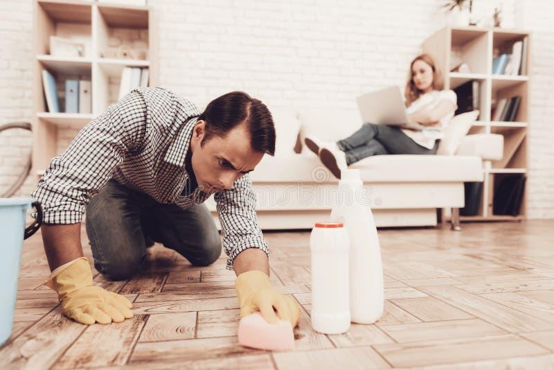 Homem com o assoalho de limpeza da toalha de rosto no apartamento fotografia de stock