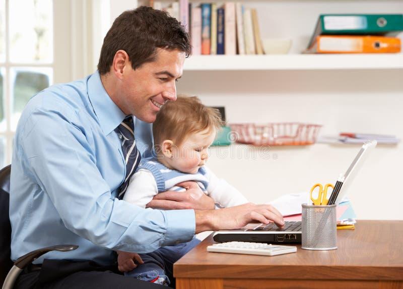 Homem com o bebê que trabalha do portátil de utilização Home