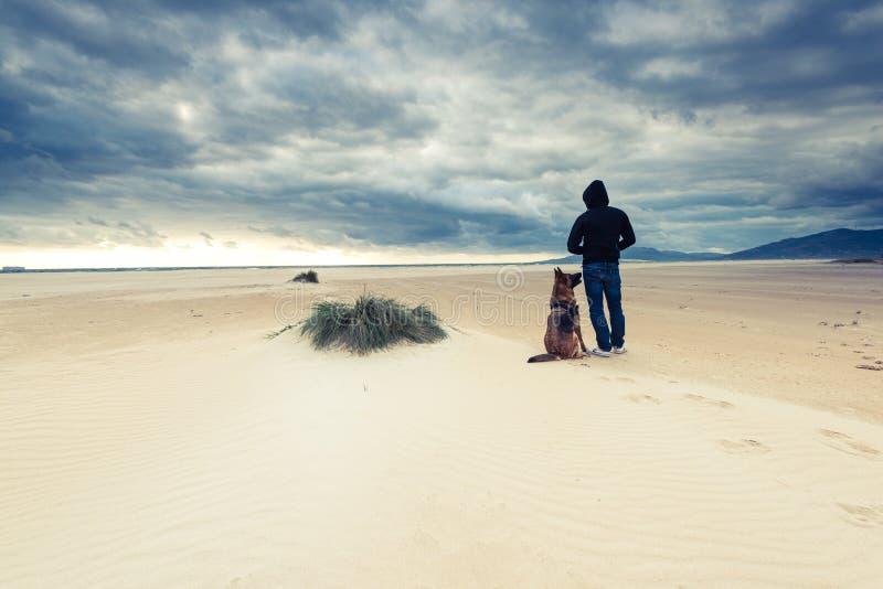 Homem com o cão na praia selvagem na tempestade fotografia de stock