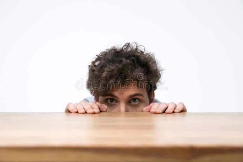 Homem com o cabelo encaracolado que espreita atrás da mesa fotos de stock