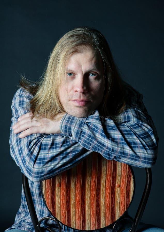 Homem com o cabelo longo que senta-se na cadeira fotografia de stock royalty free