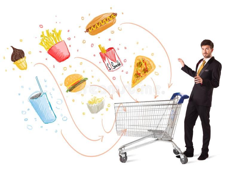 Homem com o carrinho de compras com comida lixo tóxica fotos de stock