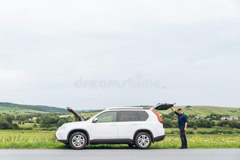 Homem com o carro quebrado no lado da estrada foto de stock royalty free
