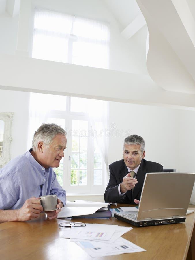 Homem com o conselheiro financeiro na tabela imagens de stock